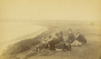 Several adults in late 19th century clothing sitting on a bluff.