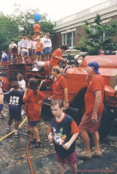Fire engine and crowd involved in the annual water fight on Main Street.