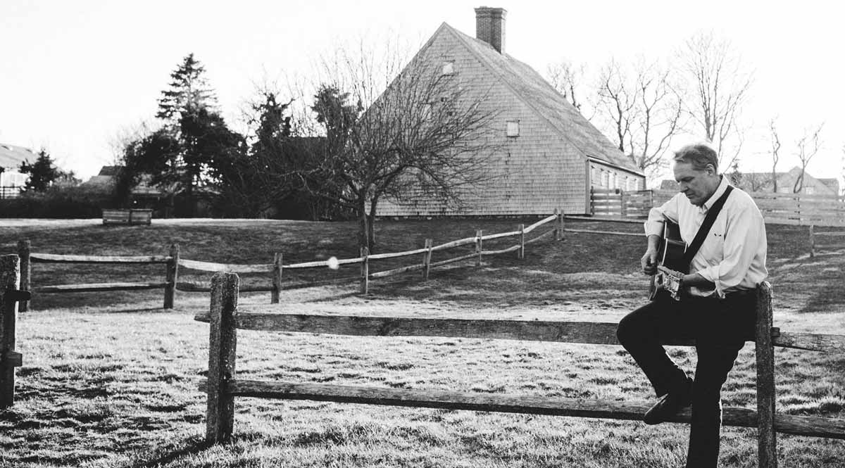 Man playing guitar while sitting on a fence with house in the background.