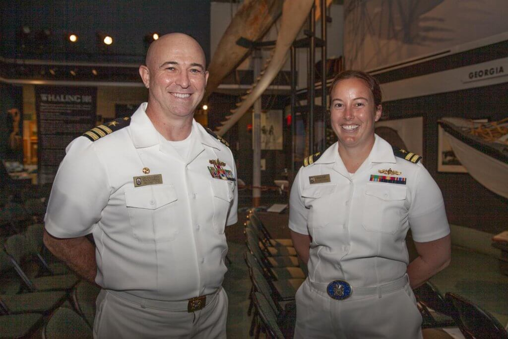 Male and female in white Navy uniform.
