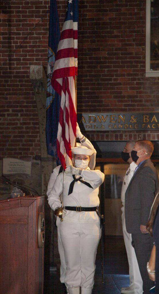 US flag being carried by person in white Navy uniform