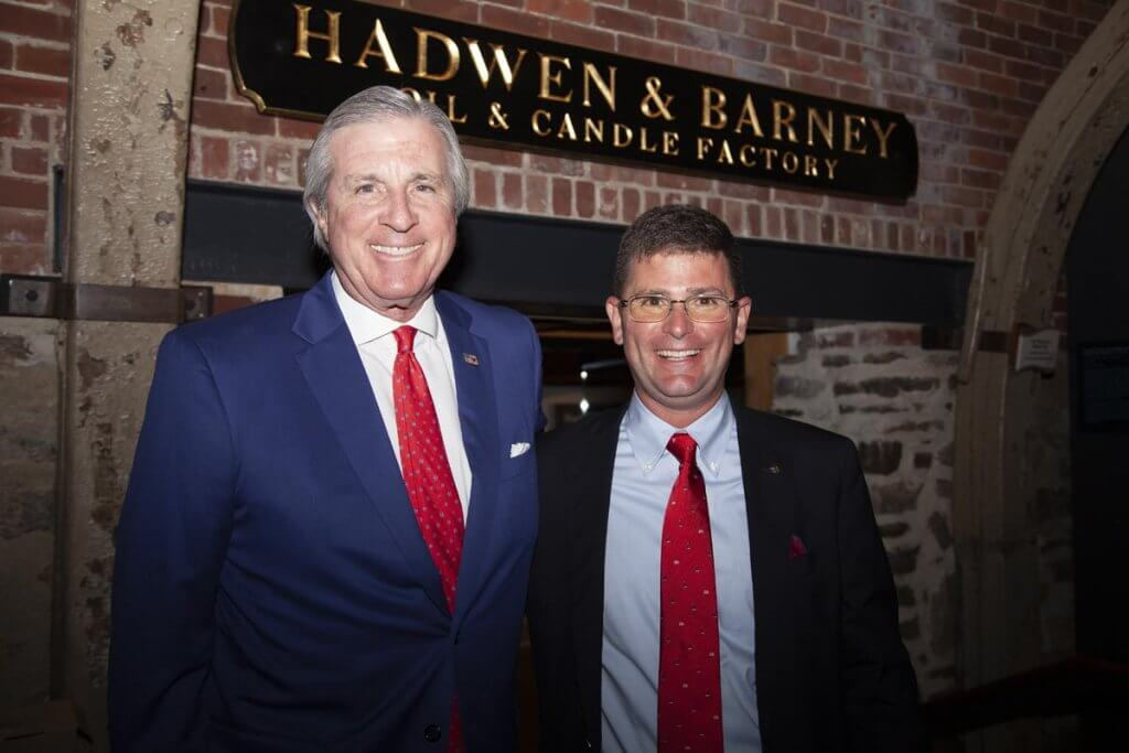 Two men in suit and red ties.