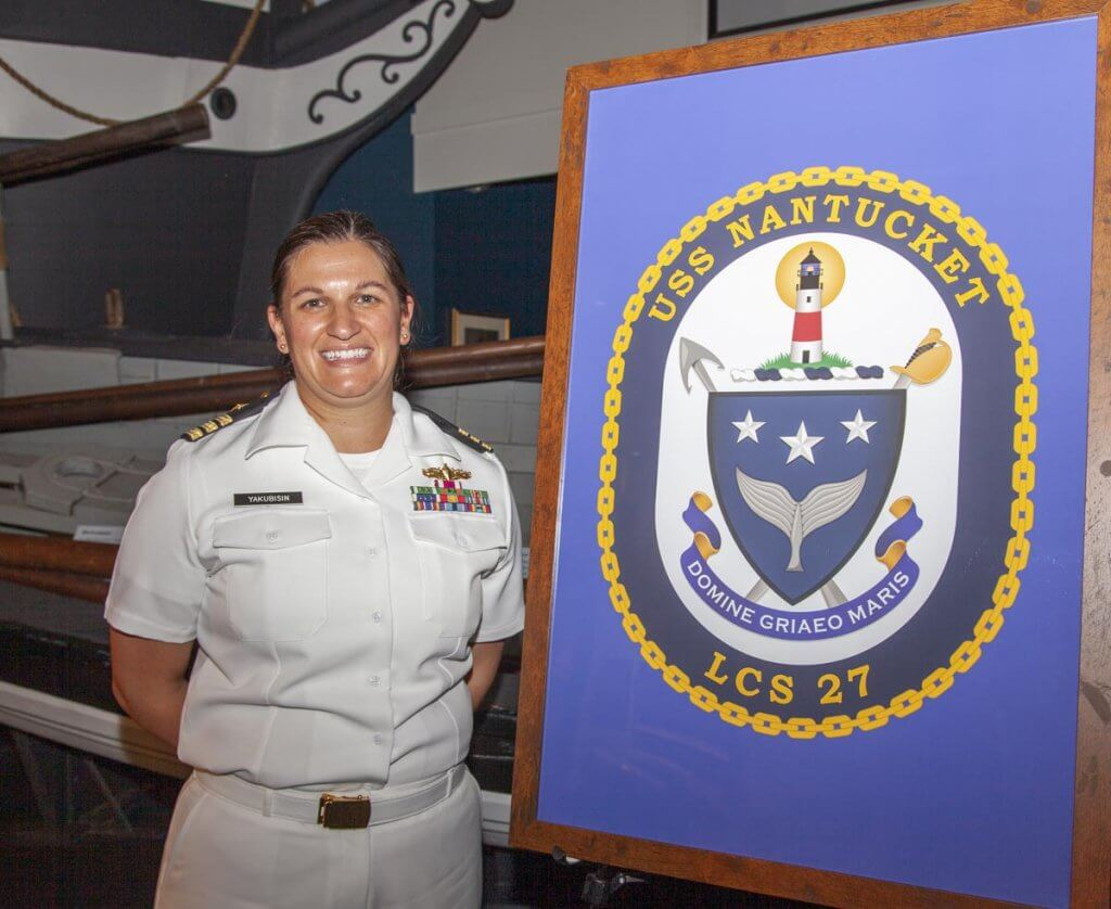 Women in white navy uniform standing next to the USS Nantucket Crest