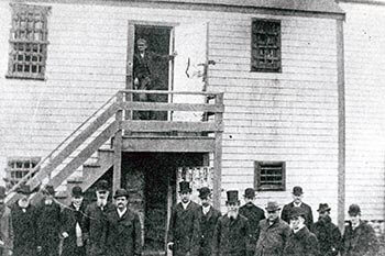 A crowd gathered in front of the jail, also known as the Old Gaol, 1893, when the Commission on Prisons inspected the jail.