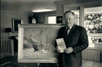 Portrait of Robert F. Mooney standing beside a painting of the shipwreck of the British Queen.