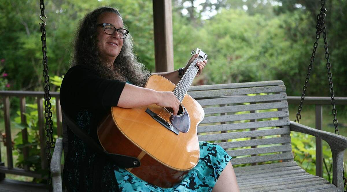 Susan Berman, Singer Songwriter playing guitar on swing.