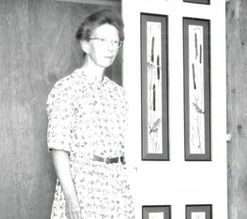 Women with glasses in a print dress.
