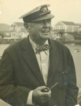 Portrait of Austin Strong, wearing a Nantucket Yacht Club cap and holding a pipe.