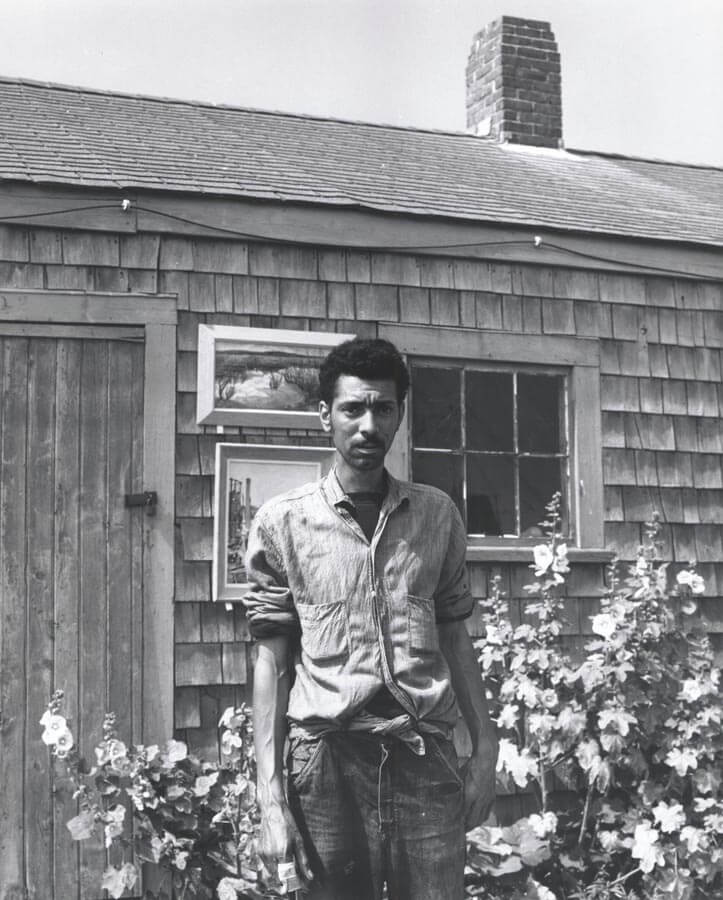 man standing in front of small house.