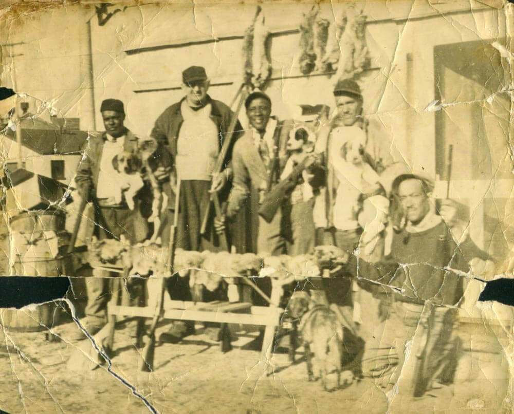 A group of men, rabbit hunters, with the spoils of their hunt, their dogs and guns.