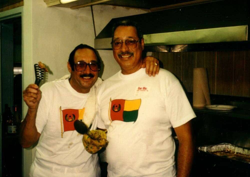 Two men cooking with Cape Verdean tshirts.