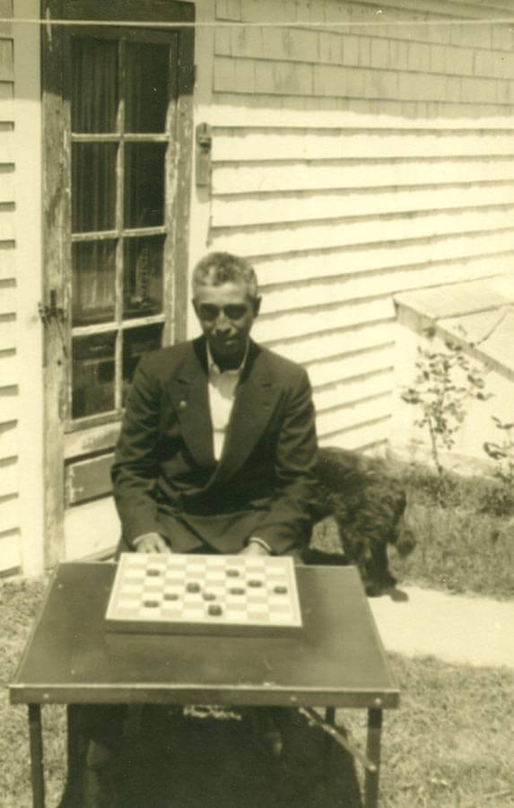 Man sitting in front of checker board.