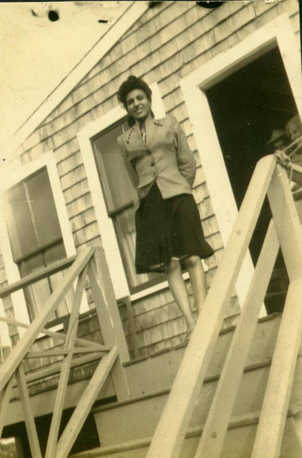 Woman standing at top of the stairs.