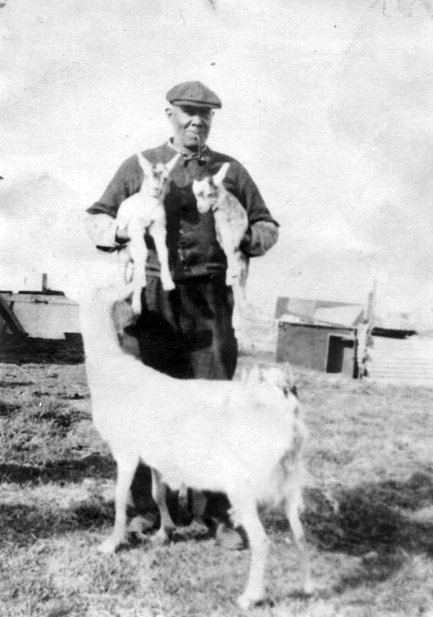 Man holding to kid goats.