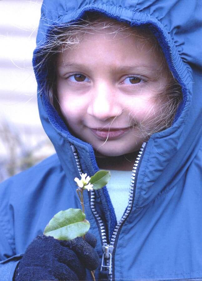 Young girl in blue jacket holding a mayflower.