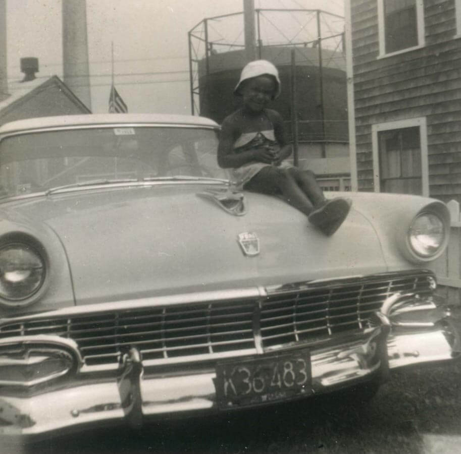 Child sitting on the hood of a 1956 Ford.
