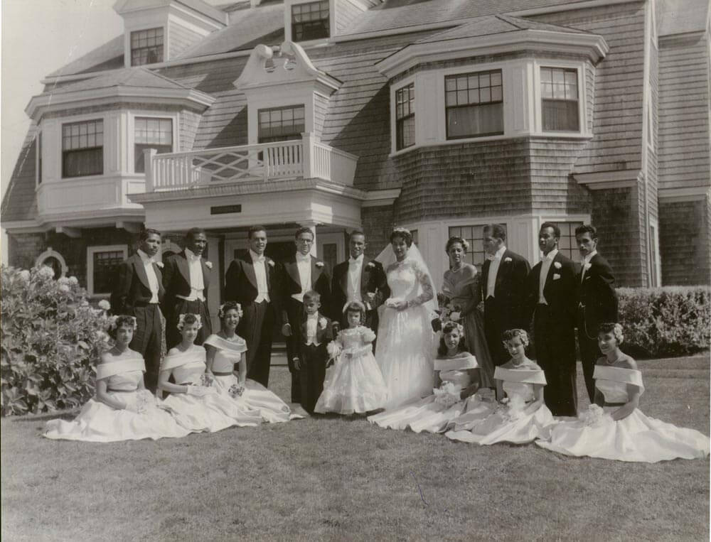 Wedding party in front of a large home.